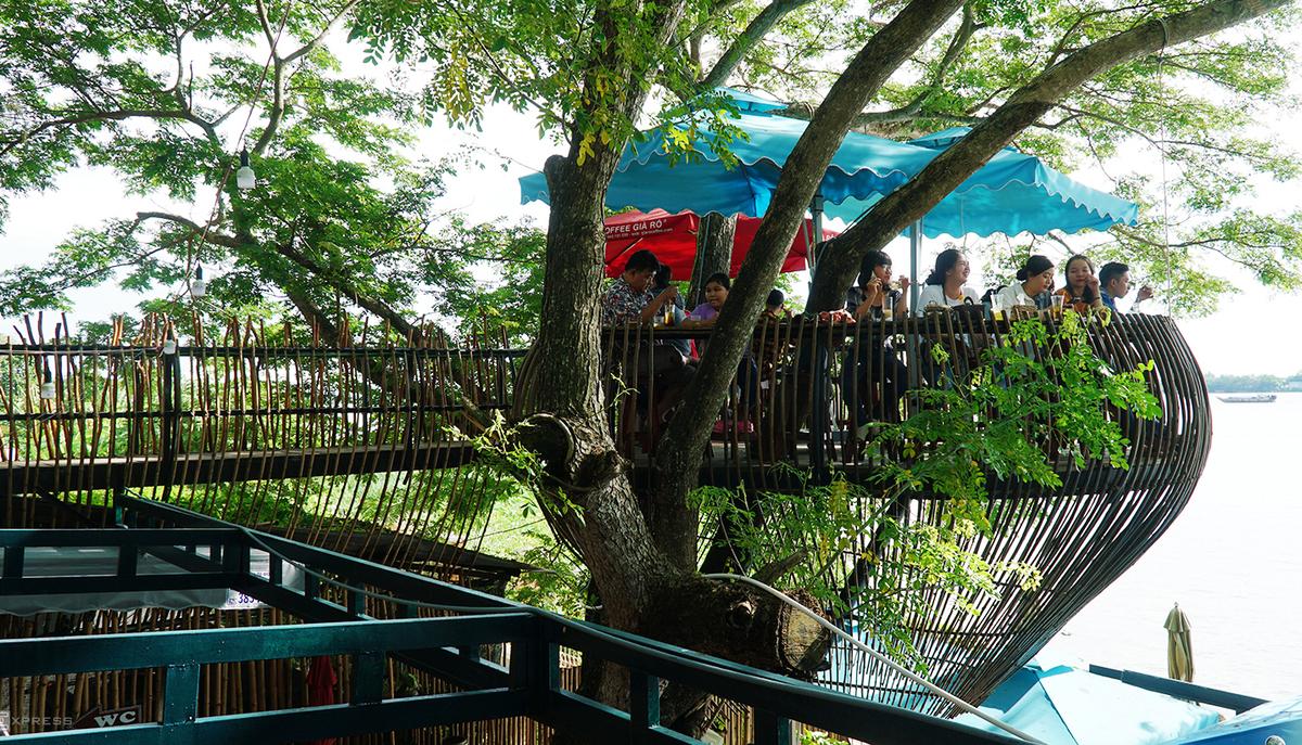 Chỗ ngồi của khách được thiết kế trên một cây cổ thụ, có hướng nhìn ra sông Hậu.